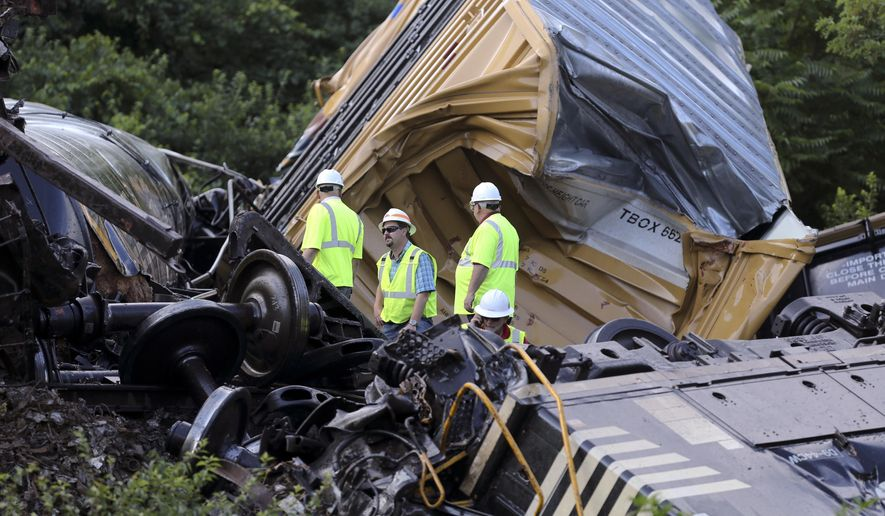 Investigators look over the wreckage of a train derailment that occurred when one westbound train struck another from behind near Dublin Va., Tuesday, July 14 2015.  (Matt Gentry/The Roanoke Times via AP)
