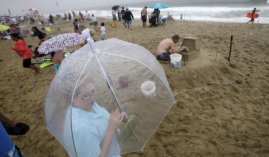 """People use umbrellas as they watch others work in the rain on their sandcastles and sculptures during the  """"NJ Sandcastle Contest,""""  contest in Belmar, N.J., Wednesday, July 15, 2015. After nearby lightning strikes during a steady rain, the beach patrol stopped the competition and asked everyone to leave the beach. (AP Photo/Mel Evans)"""