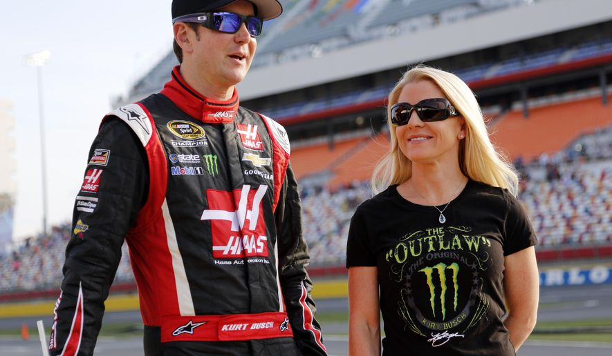 FILE - In this May 22, 2014, file photo, Kurt Busch, left, stands with Patricia Driscoll before qualifying for a NASCAR Sprint Cup series auto race at Charlotte Motor Speedway in Concord, N.C. Kurt Busch's ex-girlfriend has resigned from the veterans charity that she headed amid an investigation of her finances. A spokesman for the Armed Forces Foundation said Thursday, July 16, 2015,  that Patricia Driscoll tendered her resignation Tuesday night after 12 years as president. The foundation has posted a statement on its website that thanks Driscoll for her work but does not explain the reason for her resignation.  (AP Photo/Terry Renna, File)