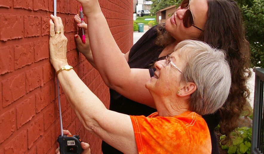 ADVANCED FOR RELEASE MONDAY, JULY 20, 2015 In this July 1, 2015, photo, artists Jessalyn Braun and Judy Beyer help prepare for the arrival of  Walldog Public Art painters when they start work on a mural on the side of the Interquest building, 304 S. Spring St., in Beaver Dam, Wis. on July 8. The recent event anticipates a mural festival in 2017 in which 12 to 15 murals will be painted throughout the downtown area. (Ken Thomas/Daily Citizen via AP)
