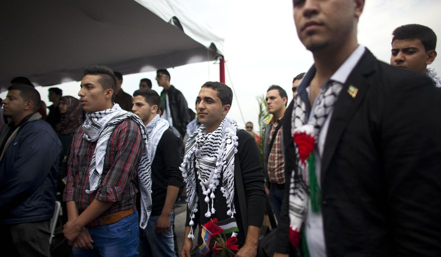 FILE - In this Nov. 6, 2014 file photo, Palestinian students attend a welcome ceremony at the Simon Bolivar airport in Maiquetia, Venezuela. The Palestinian students were greeted like celebrities upon arrival in Caracas. President Nicolas Maduro played up their symbolic importance during an address broadcast across the country. But eight months later, about a third of the Palestinians have dropped out, complaining that the program lacks academic rigor, according to interviews conducted with students, teachers and government officials. (AP Photo/Ariana Cubillos, File)