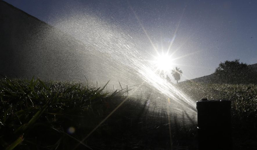 FILE - In this June 23, 2015, file photo a lawn is irrigated in Sacramento, Calif. The California Water Commission approved new rules that would essentially eliminate grass from new office and commercial buildings and reduce turf at new homes from a third of landscaped area to a quarter on Wednesday, July 15, 2015. (AP Photo/Rich Pedroncelli, File)