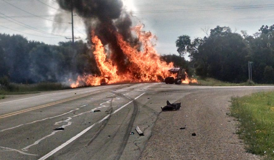 In this photo provided by the Horicon Police Department, a tanker truck carrying a load of ethanol erupts in flames after colliding with a car on a southern Wisconsin highway Thursday, July 16, 2015, near Horicon, Wis. The driver of the semi, which rolled over and ignited, escaped through a door at the top of the overturned tanker as flames burned around him, said  witness Nate Hamilton. The man had a head laceration and burns to his arm, Hamilton said.  (Joseph W. Adamson, Horicon Police Department via AP)