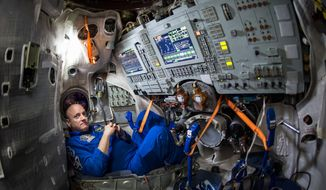 FILE - In this Wednesday, March 4, 2015 photo provided by NASA, astronaut Scott Kelly sits inside a Soyuz simulator at the Gagarin Cosmonaut Training Center (GCTC) in Star City, Russia. On Thursday, July 16, 2015, a piece of space junk forced the three International Space Station astronauts, including Kelly, to seek emergency shelter in their Soyuz spacecraft docked to the station, in case they had to make a quick getaway. (Bill Ingalls/NASA via AP)