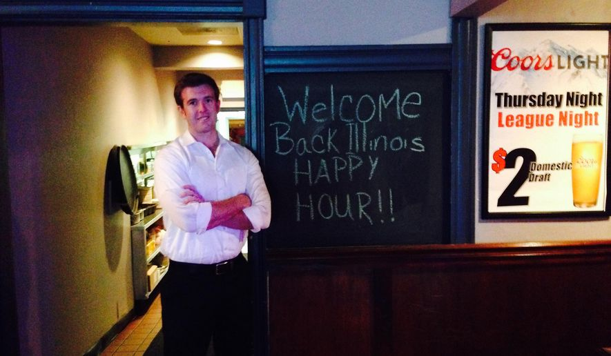 "In this, July 15, 2015 photo, Pitchers Pub and Pizzeria owner Lloyd Cueto stands in his sports bar in downtown Belleville, Ill., near a sign celebrating the repeal of the state's ban on happy hour promotions. Cueto, who is also a lawyer, hopes that after-work drink specials will draw more  business from government employees, other lawyers and judges who work at the nearby St. Clair County courthouse, but but not all bar owners are saying ""cheers"" to the new law. (AP Photo/Alan Scher Zagier)"