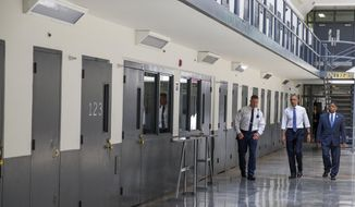President Barack Obama is led on a tour by Bureau of Prisons Director Charles Samuels, right, and correctional officer Ronald Warlick during a visit to the El Reno Federal Correctional Institution,  in El Reno, Okla., Thursday, July 16, 2015 As part of a weeklong focus on inequities in the criminal justice system, the president will meet separately Thursday with law enforcement officials and nonviolent drug offenders who are paying their debt to society at the El Reno Federal Correctional Institution, a medium-security prison for male offenders near Oklahoma City. (AP Photo/Evan Vucci)