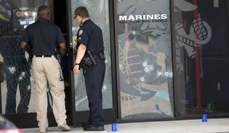 Police officers enter the Armed Forces Career Center through a bullet-riddled door after a gunman opened fire on the building Thursday, July 16, 2015, in Chattanooga, Tenn. (Associated Press)
