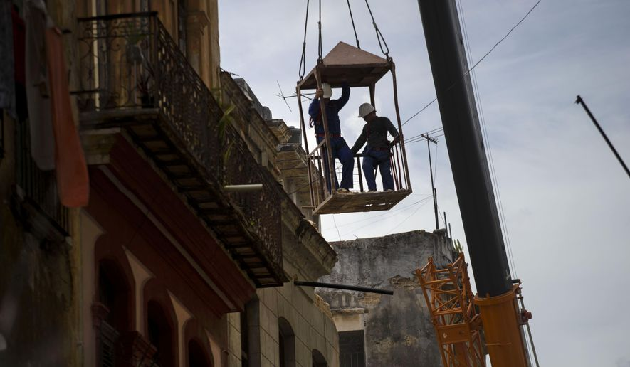 Workers in a metal box, hanging from a crane, remove the wall of a building that collapsed in Old Havana, Cuba, Thursday, July 16, 2015. Cuban officials say four people died in the Wednesday collapse, and a government statement published in Communist Party daily Granma says the two-story residence contained two family homes. (AP Photo/Ramon Espinosa)