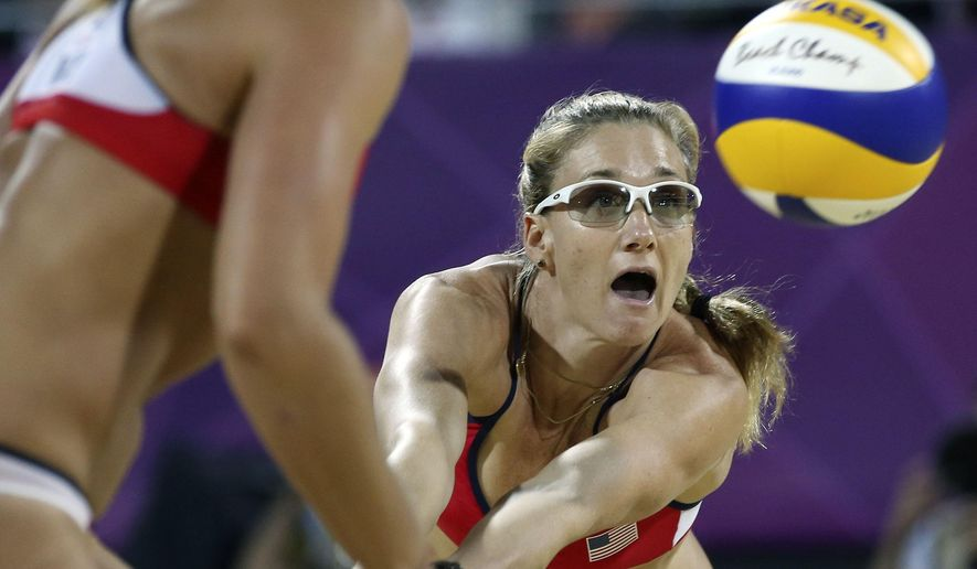 """FILE - In this Wednesday, Aug. 8, 2012 file photo, United States' Kerri Walsh Jennings, right, sets a ball for Misty May-Treanor, left, during the women's gold medal beach volleyball match at the 2012 Summer Olympics in London. Three-time beach volleyball gold medalist Kerri Walsh Jennings calls it a """"total fluke"""" she may need surgery after recently dislocating her shoulder twice, saying she still expects to compete at the 2016 Rio Olympics, Thursday, July 16, 2015.  (AP Photo/Petr David Josek, File)"""