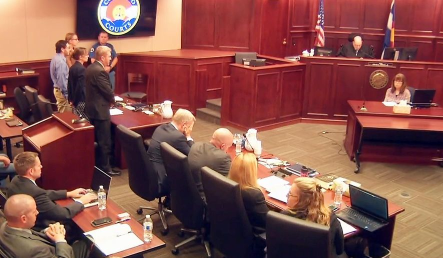 In this image taken from video, accused Colorado theater shooter James Holmes, standing on the far left, listens as the verdict is read during his trial, in Centennial, Colo., Thursday, July 16, 2015. Holmes was found guilty of murder in the deaths of 12 people in July 2012. In the center, lead prosecutor George Brauchler, puts his hands up to his face as the counts are read.  (Colorado Judicial Department via AP, Pool)