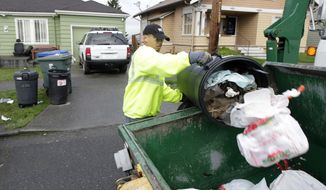 Anousone Sudettanh, an employee of Waste Management Inc., collects garbage for the city of Seattle on April 5, 2012. (Associated Press) **FILE**