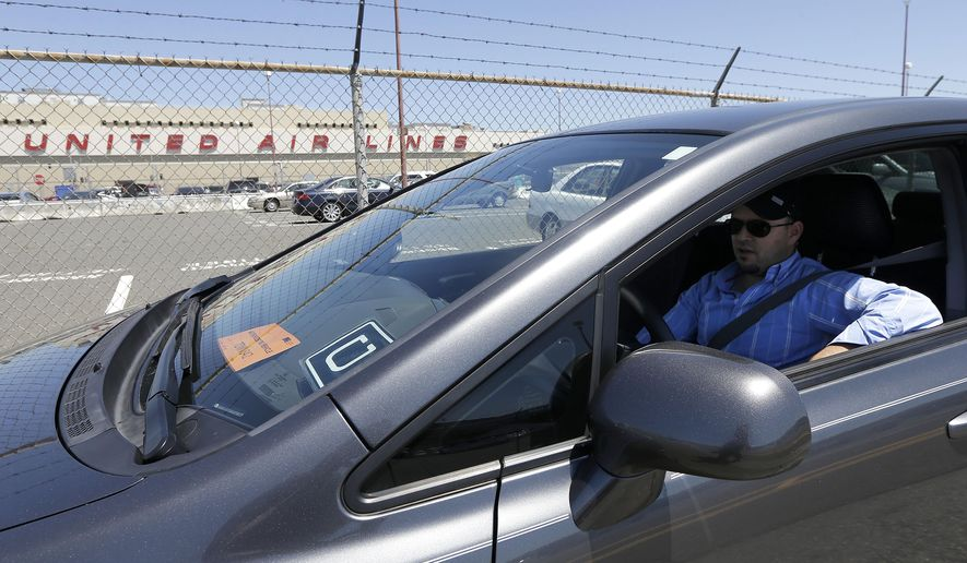 Uber driver Karim Amrani sits in his car parked near the San Francisco International Airport parking area in San Francisco, Wednesday, July 15, 2015. In the three months ended in June, Uber overtook taxis as the most expensed form of ground transportation, according to expense management system provider Certify. (AP Photo/Jeff Chiu)