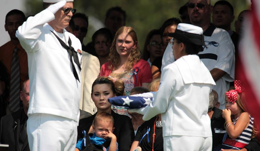 FILE - In this Aug. 3, 2012 file photo, Chantel Blunk, center, the wife of Aurora, Colo. movie theater shooting victim Jonathan Blunk, holds their son Maximus, 2, and daughter Hailey, 4, right, as a U.S. flag is prepared to present to her during a graveside service in Reno, Nev. Jonathan Blunk, 26, a Navy veteran who had served three tours in the Persian Gulf and Arabian Sea, had hoped to re-enlist to become a Navy SEAL. A friend who was injured in the theater shooting testified that Blunk threw himself in front of her and saved her life. (AP Photo/Cathleen Allison, File)