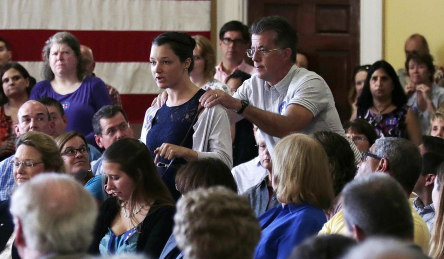 An audience guest tries to restrain an environmental activist who interrupted Democratic presidential candidate Hillary Rodham Clinton during a town hall meeting in Dover, NH, Thursday, July 16, 2015. (AP Photo/Charles Krupa)