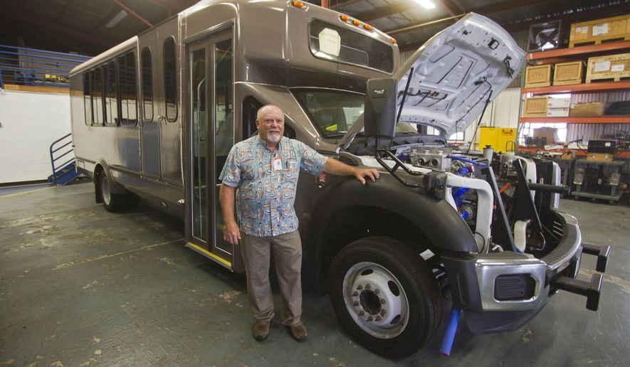 ADVANCE FOR WEEKEND OF JULY 19, 2015. In this July 10, 2015 photo, Stanley Osserman poses for a portrait next to a hydrogen-powered shuttle bus at the Hawaii Center for Advanced Transportation Technologies in Honolulu. Hydrogen-powered vehicles are beginning to roll onto Hawaii's transportation scene. Two 25-seat hydrogen-powered buses will soon be shuttling tourists between the visitors center and the Thurston Lava Tube at Hawai'i Volcanoes National Park, and hydrogen might someday fuel the Wiki-Wiki shuttles at Honolulu Airport. (Dennis Oda/ The Star-Advertiser via AP)