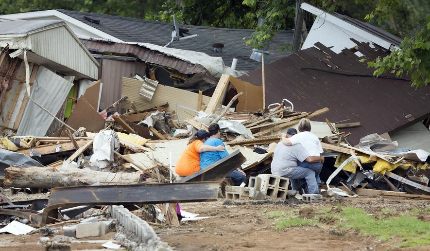 Members of the Cisco family comfort each other during a break from searching through debris after deadly flooding in Flat Gap, Ky., Wednesday, July 15, 2015. Searches and cleanup continued after flash floods in northern Johnson County outside of Paintsville destroyed homes and vehicles and residents were reported missing. (AP Photo/David Stephenson)