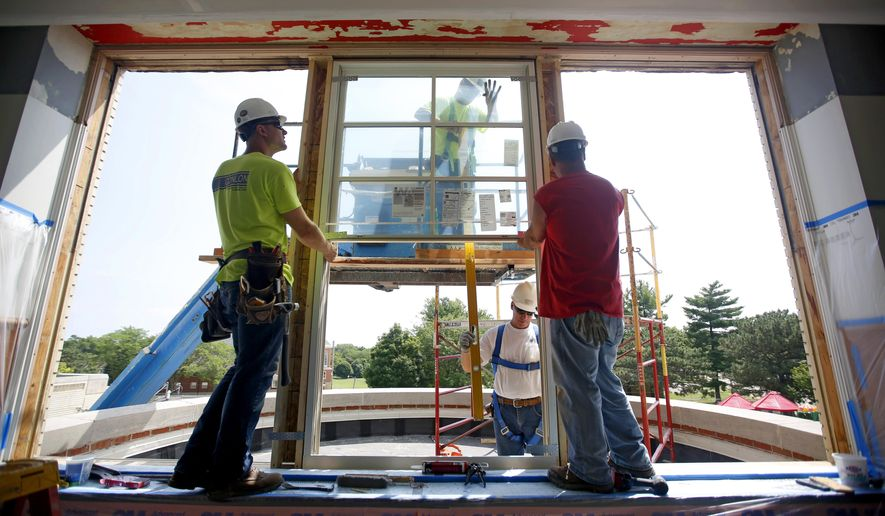 In this photo taken on Wednesday, July 15, 2015, Chris Esch, left, and Tony Ede, both of Conlon Construction Co., install a new window as Bryant Elementary School undergoes renovations, in Dubuque, Iowa, John and Alice Butler donated $780,000 to help replace and renovate nearly 90 windows and around 10 doors at the school. (Mike Burley/Telegraph Herald via AP) MANDATORY CREDIT