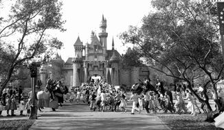 In this Sunday, July 17, 1955 photo, children sprint across a drawbridge and into a castle that marks the entrance to Fantasyland at the opening of Walt Disney's Disneyland in Anaheim, Calif. Fantasyland had been closed until late in the day. (AP Photo/FILE)