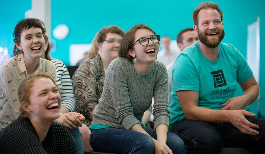 ADVANCE FOR SATURDAY JULY 18 AND THEREAFTER - In a July 2, 2015 photo, Graduating students Clare Jacky, foreground, and Mary White, Kaitlin Muth and Vince Jones, left to right, laughduring a speech from a fellow student at a graduation ceremony for new software engineers at Prime Digital Academy in Bloomington, Minn. It was the first class to graduate from the Twin Cities school that aims to diversify the tech industry.   (Jennifer Simonson/MPR News via AP)