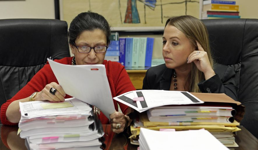 In this photo taken July 16, 2015, attorneys Grisel Ybarra, left, and Monica Barba Neumann look over documents at their office in Miami. Ybarra and Neumann represent several clients who could face deportation. With the US and Cuba inching closer to fully restoring diplomatic ties, including re-opening embassies for the first time in 54 years, the future is murky for tens of thousands of Cuban immigrants who have been ordered by immigration authorities to leave the country. As many as 25,000 immigrants who have outstanding deportation orders live in the U.S. legally but are considered priorities for immigration enforcement agents, according to data maintained by Immigration and Customs Enforcement. Those priorities include people with serious criminal convictions or who pose a threat to national security. (AP Photo/Alan Diaz)