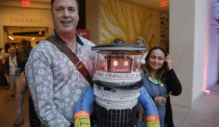 Co-creator David Harris Smith carries hitchBOT, a hitchhiking robot, during its' introduced to an American audience at the Peabody Essex Museum Thursday, July 16, 2015, in Salem, Mass. HitchBOT is set to embark on its' first cross-country hitchhiking trip of the U.S., after completing similar tips in Canada and Europe. The plans are for hitchBot to leave the Boston area Friday with a final destination goal of reaching San Francisco. (AP Photo/Stephan Savoia)