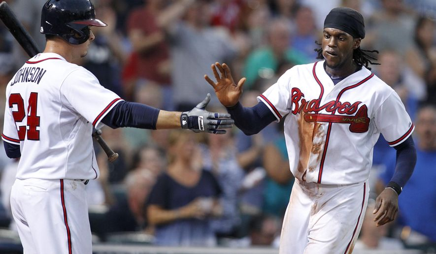 Atlanta Braves' Cameron Maybin, right, celebrates with Kelly Johnson after scoring on a Nick Markakis double during the third inning of a baseball game against the Chicago Cubs, Friday, July 17, 2015, in Atlanta. (AP Photo/Brett Davis)