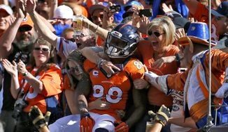 FILE - In this Oct. 5, 2014, file photo, Denver Broncos wide receiver Demaryius Thomas (88) celebrates his touchdown against the Arizona Cardinals with fans during the first half of an NFL football game in Denver. Demaryius Thomas is the highest-paid player in Denver Broncos history, Now, general manager John Elways says, much more will be expected of the three-time Pro Bowl receiver. (AP Photo/Jack Dempsey, File)