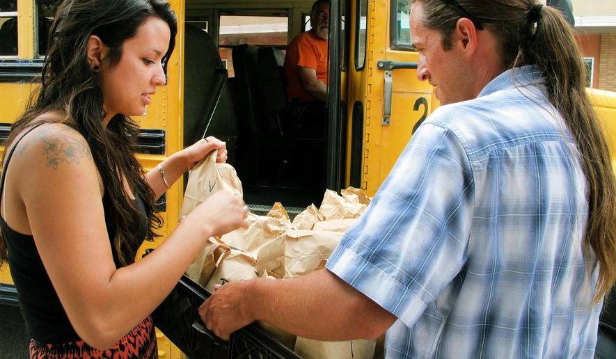 Stefany Olivas, left, and Casey Coty with the SouthWest Organizing Project prepare to hand out sack lunches as they leave Albuquerque, N.M., on Friday, July 17, 2015, for a public hearing in Santa Fe to speak against New Mexico's proposal to impose work and job training requirements for low-income New Mexicans who receive food stamps. The New Mexico Human Services Department plans to phase in the changes beginning in October. (AP Photo/Susan Montoya Bryan)