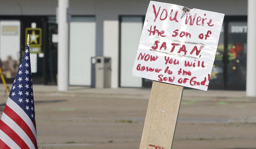 A sign and a flag is placed at a make-shift memorial outside a military recruiting center on Friday, July 17, 2015, in Chattanooga, Tenn. Muhammad Youssef Abdulazeez of Hixson, Tenn.,  attacked two military facilities on Thursday, in a shooting rampage that killed four Marines. (AP Photo/John Bazemore)