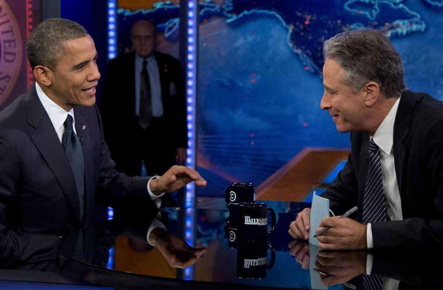 """FILE - In this Oct. 18, 2012 file photo, President Barack Obama talks with Jon Stewart during a taping of his appearance on """"The Daily Show with John Stewart"""" in New York. Obama is booked for his seventh appearance on """"The Daily Show"""" Tuesday as Jon Stewart is beginning his final three weeks as host of the show. Stewart announced earlier this year that he will be leaving """"The Daily Show"""" after 16 years. His final broadcast will be on Aug. 6. (AP Photo/Carolyn Kaster, File)"""