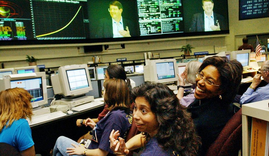 FILE - In this Sept. 21, 2003, file photo, Claudia Alexander, right, project manager for Galileo, waits in the mission control room in Pasadena, Calif., along with engineer Nagin Cox, center, and others for the spacecraft to take its final plunge into Jupiter. Alexander, a pioneering scientist who helped direct NASA's Galileo mission to Jupiter and the international Rosetta space exploration project, has died Saturday, July 11, 2015, after a long battle with breast cancer. She was 56. (AP Photo/Ric Francis, File)