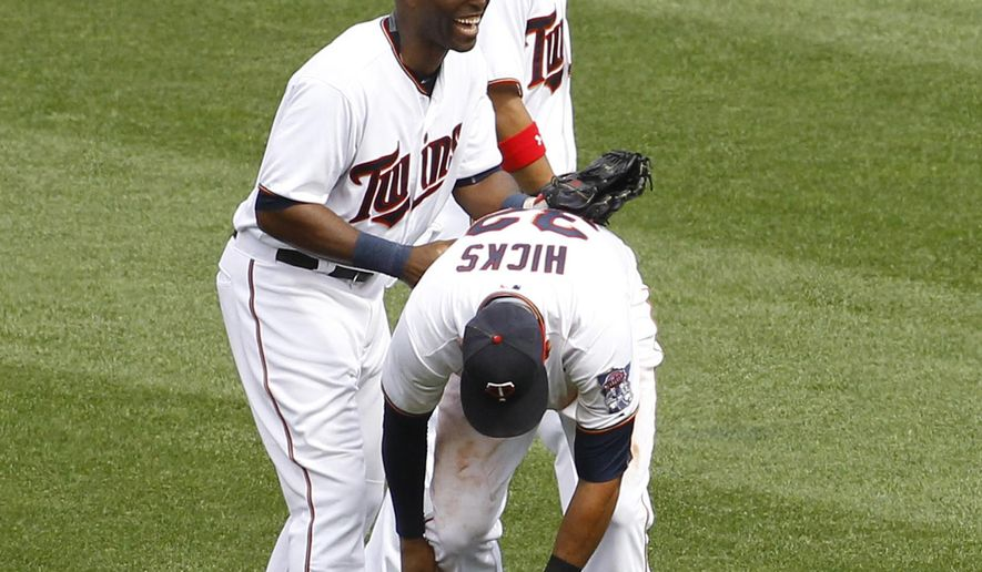 Minnesota Twins right fielder Torii Hunter, left, and left fielder Eddie Rosario, right, share a laugh after a failed celebration leap with center fielder Aaron Hicks (32) after the Twins defeated the Detroit Tigers 7-1 in a baseball game in Minneapolis, Sunday, July 12, 2015.  (AP Photo/Ann Heisenfelt)