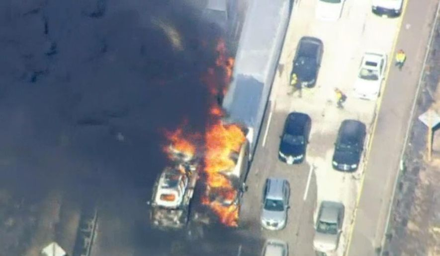 In this frame from video provided by NBC4, smoke rises from vehicles as a fast-moving wildfire swept across a freeway Friday, July 17, 2015, near Hesperia, Calif. The fire swept by desert winds burned on both sides of Interstate 15, the main connector between Southern California and Las Vegas that was crowded with vehicles. (NBC4 via AP)