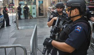 Officers with the NYPD anti-terrorism unit guard a military recruiting station in Times Square, Friday, July 17, 2015, in New York.  Security at military recruiting and reserve centers will be reviewed in the aftermath of a deadly shooting in Tennessee. (AP Photo/Bebeto Matthews)