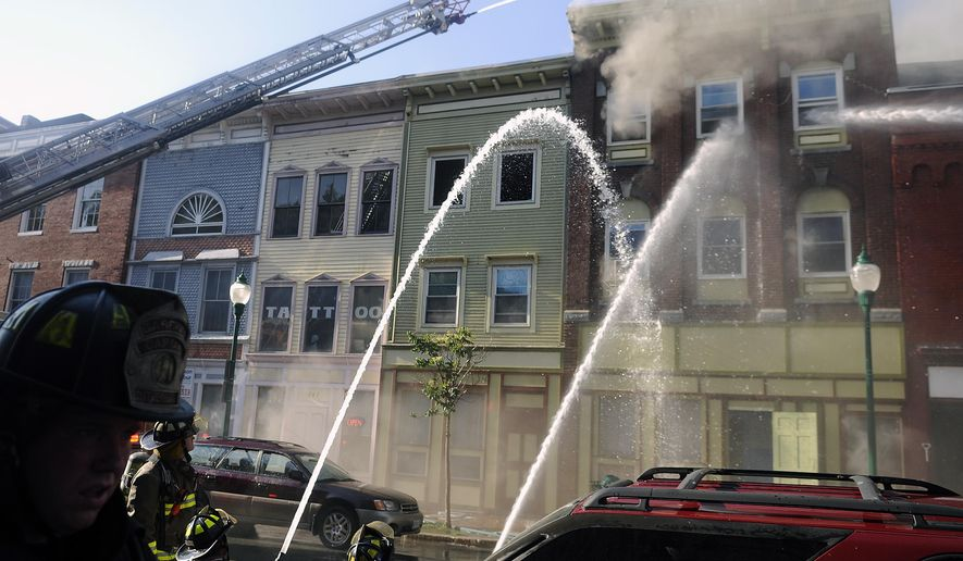 "Firefighters deploy water on the blaze on the fourth floor of a building in Gardiner, Maine, on Thursday, July 16, 2015. Authorities say four people are unaccounted for following a fire that swept through four buildings. Fire Marshal Joe Thomas said that two missing people were believed to be tenants of the building where the fire apparently started Thursday and may have lived in apartments where the roof later collapsed. Gardiner Mayor Thom Harnett called the fire a ""community disaster."" (Andy Molloy/The Kennebec Journal via AP)"