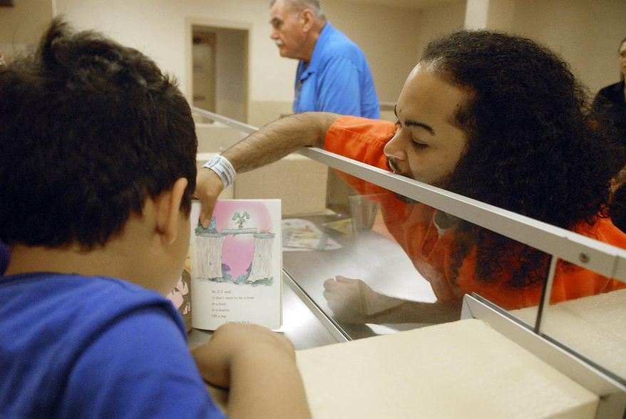 In this photo taken on Monday, July 13, 2015, inmate Carlos Diaz-Hernandez reads with his children, who are currently in foster care, during the Reading is Fun Program (RIF) at the Schenectady County Jail's visitation room, in Schenectady, N.Y. (Erica Miller /The Daily Gazette via AP)  TROY, SCHENECTADY; SARATOGA SPRINGS; ALBANY AND AMSTERDAM OUT; MANDATORY CREDIT