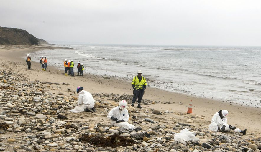 FILE - Int his June 10, 2015, file photo, Shoreline Cleanup Assessment Technique team members evaluate oil coverage, far left, as workers clean up areas affected by an oil spill at Refugio State Beach, north of Goleta, Calif. Nearly two months after an oil pipeline break fouled beaches near Santa Barbara, California, the costly cleanup is about finished, officials said Thursday, July 16, 2015. (AP Photo/Damian Dovarganes, File)