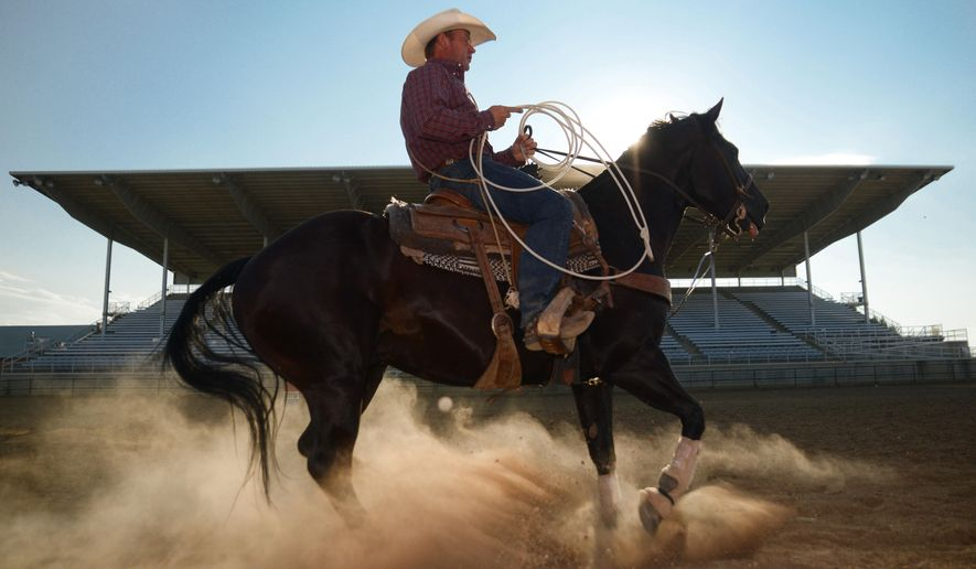 Sheridan, Wyoming, cowboy J.R. Olson warms up his horse Hollywood before practicing steer roping at the Sheridan County Fairgrounds Arena. Olson practices roping around his work schedule as a floor installer. Olson is competing in the Sheridan WYO Rodeo for the first time since his injury six years ago. (Justin Sheely/The Sheridan Press via AP)