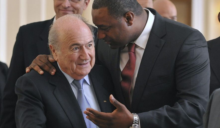 FILE - In this May 23, 2012,  file photo,  newly elected president of CONCACAF Jeffrey Webb, right,  talks to FIFA President Sepp Blatter as they arrive at the meeting of the Confederation of North, Central American and Caribbean Association Football prior to the two-day congress of FIFA in Budapest, Hungary. Webb has been extradited to the United States following his arrest in Switzerland on racketeering and bribery charges filed by American prosecutors. The Swiss Federal Office of Justice said Thursday, July 16, 2015, the man was extradited a day earlier after 50 days of detention. U.S. authorities have said more indictments could follow, and FIFA President Sepp Blatter is a target of the widening case. (Szilard Koszticsak/MTI via AP, File)