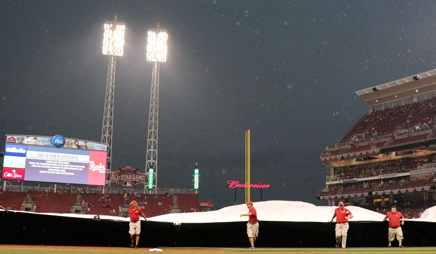 The grounds crew pulls a tarp to cover the infield as rain delays a baseball game between the Cleveland Indians and the Cincinnati Reds during the third inning, Friday, July 17, 2015, in Cincinnati. (AP Photo/Gary Landers)