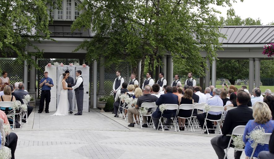 In this June 19, 2015 photo, Danessa Molinder and Billy Castrodale get married in the open air courtyard at the Community Life Center, in Indianapolis. The somewhat ironically named Community Life Center sits on cemetery land near a funeral home and also has hosted proms, community banquets and even a breakfast with Santa. (AP Photo/Darron Cummings)