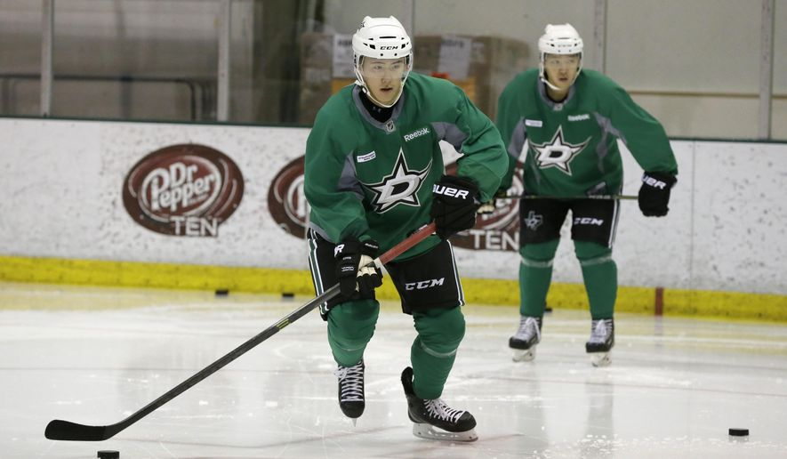 Wonjun Kim, left, of South Korea, takes a puck in front of fellow South Korean Jinhui Ahn during a Dallas Stars development hockey camp at the team's practice facility in Frisco, Texas, Thursday, July 9, 2015. South Korean players from the Asia League Ice Hockey are working out with the Stars. (AP Photo/LM Otero)