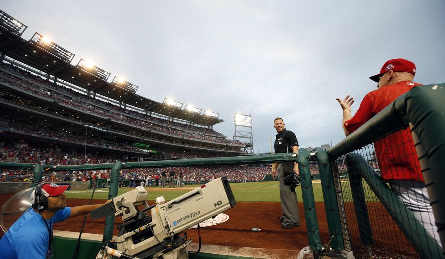 Home plate umpire Jim Wolf (28) talks with Washington Nationals manager Matt Williams (9) after some of the lights went out and play was halted during the fourth inning of a baseball game against the Los Angeles Dodgers at Nationals Park, Friday, July 17, 2015, in Washington. (AP Photo/Alex Brandon)