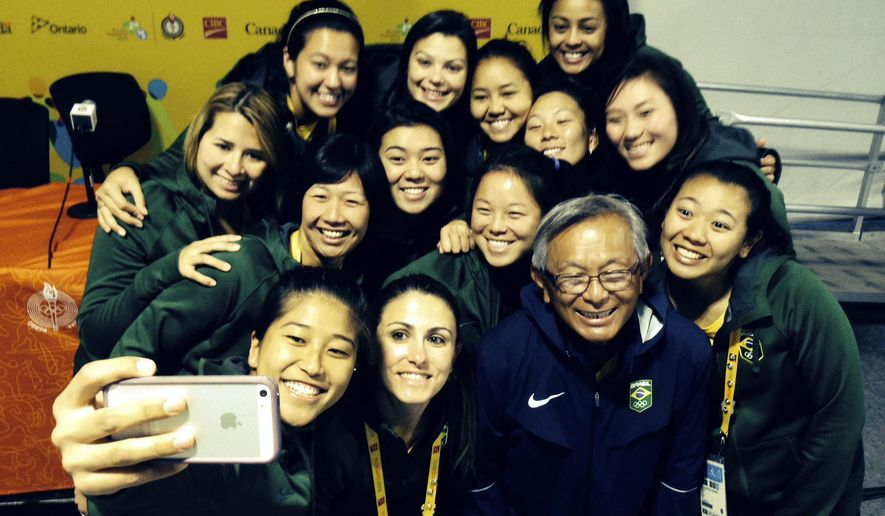 CORRECTS NAME - Brazil's national women's softball team-member Samira Tanaka, takes a group selfie of her teammates and her coach Taketomi Higashi, second from right, bottom, at the athletes village after their practice was canceled due to rain during the 2015 Pan Am games in Toronto, Friday July 17, 2015. When Brazil's women's softball team takes the field in the Pan Am Games, they won't look much like the stereotypical image of Brazil. Almost all the players have roots in Japan, where softball is very popular. About 2 million Brazilians claim Japanese ancestry, the largest Japanese immigrant community in the world. (AP Photo/Steve Wade)