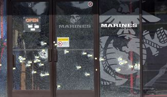 Yellow pieces of paper mark bullet holes in the glass at a military recruiting center on Friday, July 17, 2015, in Chattanooga, Tenn. Muhammad Youssef Abdulazeez of Hixson, Tenn., attacked two military facilities on Thursday, in a shooting rampage that killed four Marines. (AP Photo/John Bazemore)