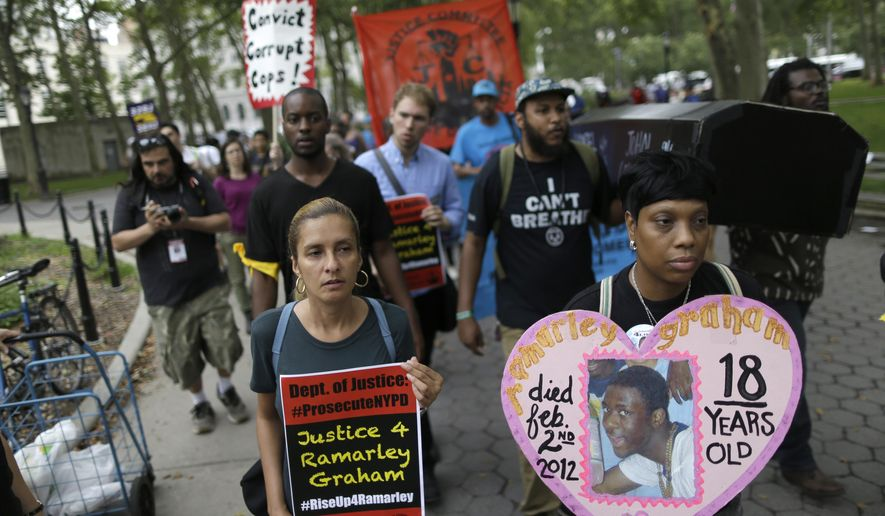 Constance Malcolm, right, the mother of Ramarley Grahamm, leads a procession with symbolic coffins during a rally, Saturday, July 18, 2015, in New York. Several hundred people rallied outside the federal courthouse in Brooklyn on Saturday to demand action in the fatal chokehold death of Eric Garner by a white police officer. (AP Photo/Mary Altaffer)