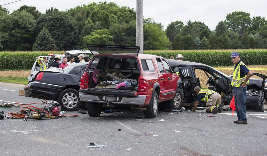 Authorities investigate the scene of a fatal crash between a limousine and sports utility vehicle Saturday, July 18, 2015, in Cutchogue, N.Y. Multiple visitors to New York wine country were killed Saturday and others were seriously injured in the crash on the eastern end of Long Island, law enforcement officials said. (Randee Daddona/Newsday via AP)  NYC LOCALS OUT; MANDATORY CREDIT
