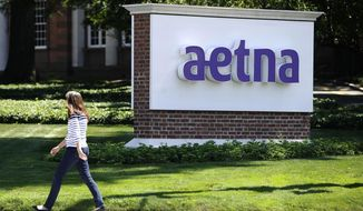 In this Tuesday, Aug. 19, 2014 file photo, pedestrian walks past a sign for health insurer Aetna Inc., at the company headquarters in Hartford, Conn. (AP Photo/Jessica Hill, File)