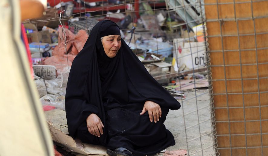 An Iraqi woman grieves at the site of a deadly Friday night suicide car bombing at a busy market in Khan Beni Saad, about 20 miles (30 kilometers) northeast of Baghdad, Iraq, Saturday, July 18, 2015. (AP Photo/Karim Kadim)