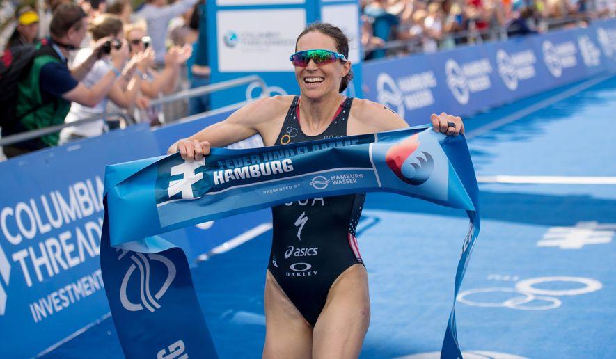 Gwen Jorgensen, from the U.S.  crosses the finish line to win the women's triathlon in Hamburg, northern Germany, Saturday, July 18, 2015.  (Daniel Reinhardt/dpa, via AP)
